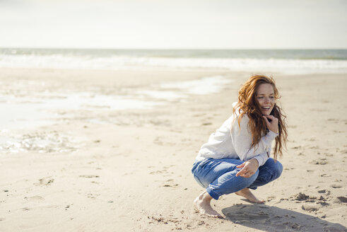 Redheaded woman relaxing on the beach, crouching - KNSF04323