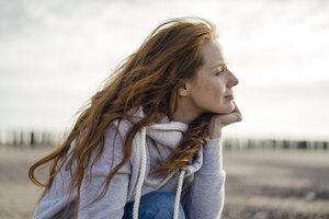 Redheaded woman enjoying fresh air at the beach - KNSF04335