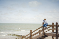 Woman sitting on fence at the beach, relaxing at the sea - KNSF04338