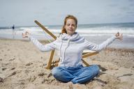 Woman sitting cross-legged on sand, meditating on the beach - KNSF04341