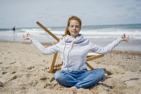 Woman sitting cross-legged on sand, meditating on the beach - KNSF04341