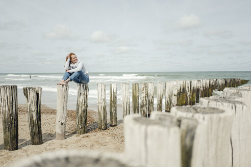 Woman sitting on fence at the beach, relaxing at the sea - KNSF04344