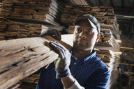 A heap of recycled reclaimed timber planks of wood. Environmentally responsible reclamation in a timber yard. A man carrying a large plank of splintered rough wood. - MINF01817
