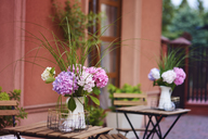 Poland, Debica, street cafe, table with flowers - ABIF00725