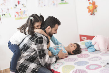 Father playing with his children in bedroom - JASF01900