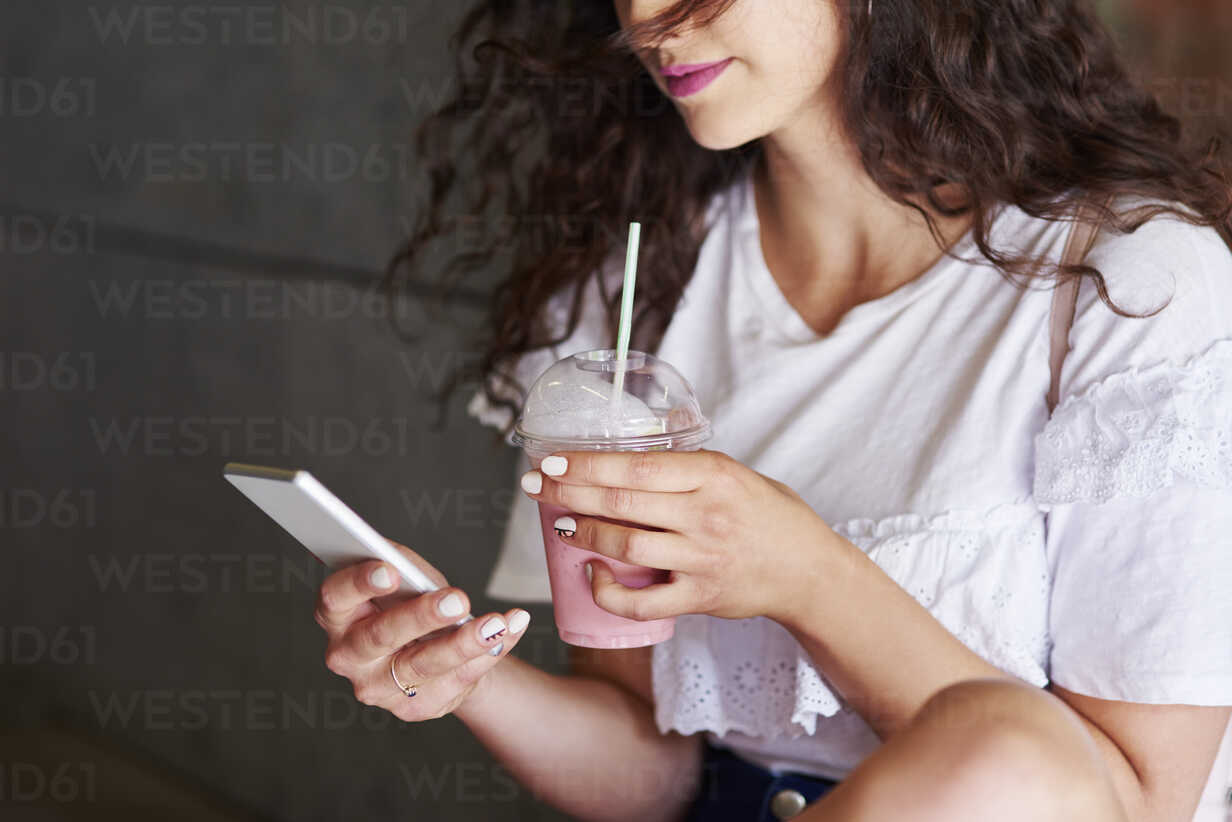 Woman's hands holding smartphone and plactic cup of smoothie - ABIF00745 - gpointstudio/Westend61