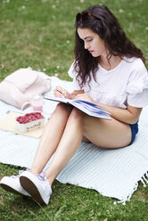 Young woman sitting on blanket on a meadow writing in notebook - ABIF00748