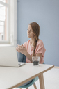 Woman at home sitting at desk with laptop - JOSF02307