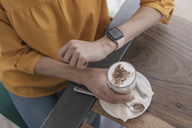 Woman wearing smartwatch, sitting in cafe, drinking coffee - JOSF02322