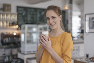 Young business owner standing in her coffee shop, drinking coffee - JOSF02325