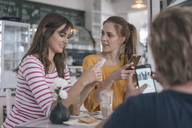 Two girlfriends meeting in a coffee shop, using smartphones - JOSF02343