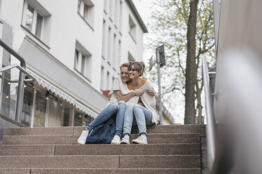 Friends sitting on stairs in the city, sharing cardigan - JOSF02346