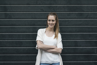 Portrait of a pretty woman in front of roller shutter - JOSF02349