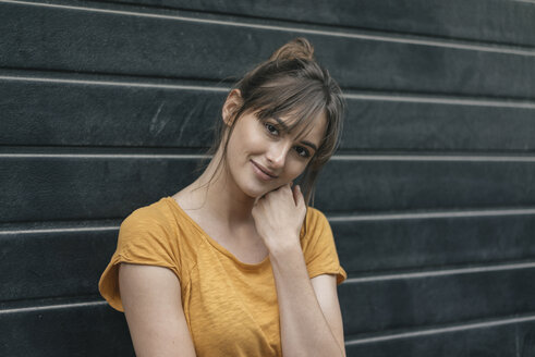 Portrait of a pretty woman in front of roller shutter - JOSF02352
