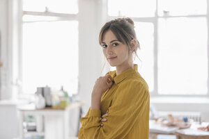 Portrait of a young woman at home, wearing a yellow blouse - JOSF02355