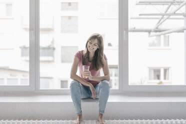 Woman sitting on window sill, holding a glass - JOSF02361