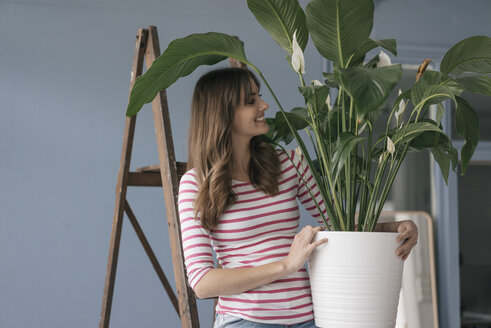 Woman holding potted plant in her bew home - JOSF02364