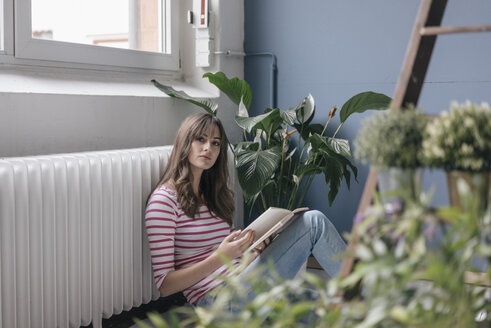 Woman sitting on ground in her new home, reading a book, surrounded by plants - JOSF02367