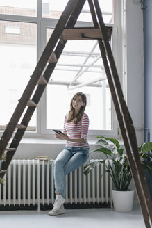 Woman sitting on radiator in her new home, reading e-book, surrounded by plants - JOSF02370