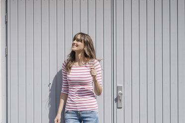 Young woman standing in front of garage doorm enjoying the sunshine, listening music - JOSF02373