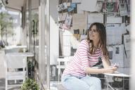 Woman sitting in coffee shop, enjoying the sunshine - JOSF02376