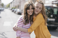 Two girlfriends embracing in the city - JOSF02403