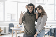 Man wearing chimpanzee mask, making victory-sign, woman leaning on him - JOSF02409