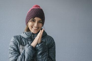 Woman wearing woolly hat in snow, portrait - JOSF02412
