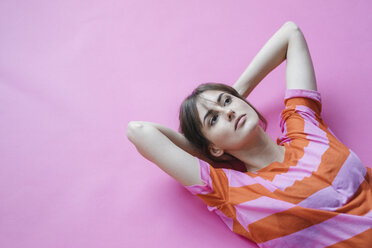 Woman lying on pink background with hands behind head, thinking - JOSF02421