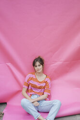 Confident young woman sitting on pink background - JOSF02427