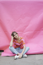Confident young woman sitting on pink background - JOSF02430