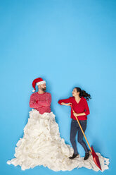 Couple shoveling snow, man wearing Santa hat - BAEF01635