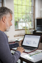 Mature man working in his home office at a loft apartment - FKF03039