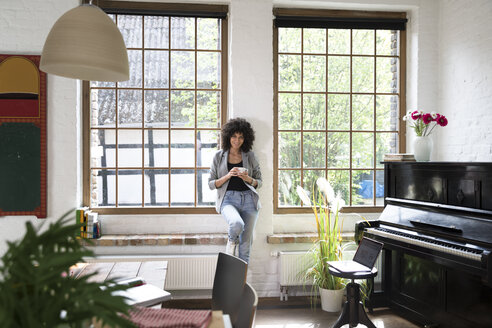 Woman standing at window of her loft apartment, drinking coffee - FKF03051