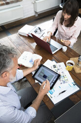 Mature couple working from their home office, using laptop and digital tablet - FKF03069