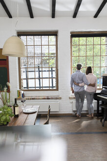 Mature couple standing in their comfortable loft, looking out of window, rear view - FKF03078
