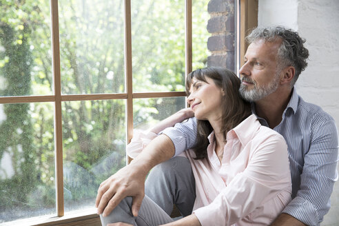 Mature couple sitting on window sill, looking out of window - FKF03081