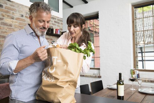 Mature man bringing grocery bag full of purchase to the kitchen - FKF03084