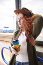 Portrait of redheaded woman with coffee to go and smartphone waiting at platform - ABIF00761