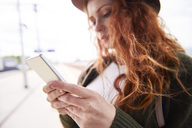 Hans of redheaded woman holding smartphone - ABIF00764