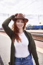 Portrait of smiling redheaded woman with brown hat at platform - ABIF00767