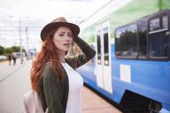 Portrait of redheaded woman waiting at platform - ABIF00770