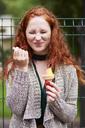 Portrait of freckled redheaded woman eating icecream - ABIF00776