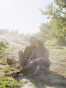 Apple orchard. A couple sitting on a sunlit path. - MINF02276