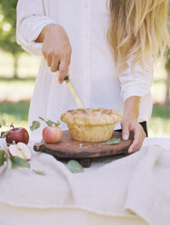 Apple orchard. Woman standing at a table with food, cutting an apple pie. - MINF02279