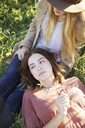 Apple orchard. Two women lying in the grass. - MINF02297