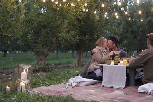 Apple orchard. Couple sitting on the ground, kissing, food and drink on a table. - MINF02300