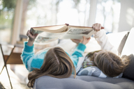 Two girls lying on a sofa on their back, reading a book. - MINF02303