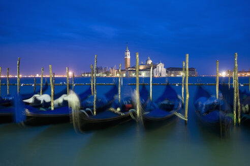 A view from the Riva degli Schiavoni and the Piazza San Marco across the water to the island and church of San Giorgio Maggiore. Gondolas moored at dusk. - MINF02363