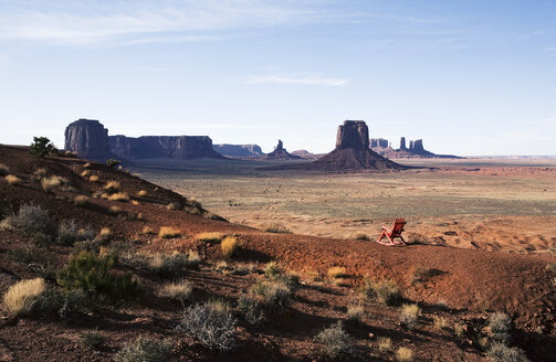 The landscape and eroded sandstone buttes and structure of Monument Valley. A single wooden chair. - MINF02378